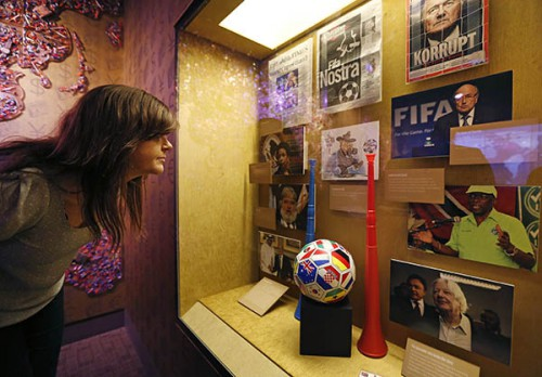 """Krissi Reeves looks at a display on FIFA at the Mob Museum Tuesday, Sept. 1, 2015, in Las Vegas. A display on FIFA corruption titled """"The 'Beautiful Game' Turns Ugly""""opens at the museum Tuesday. (AP Photo/John Locher)"""